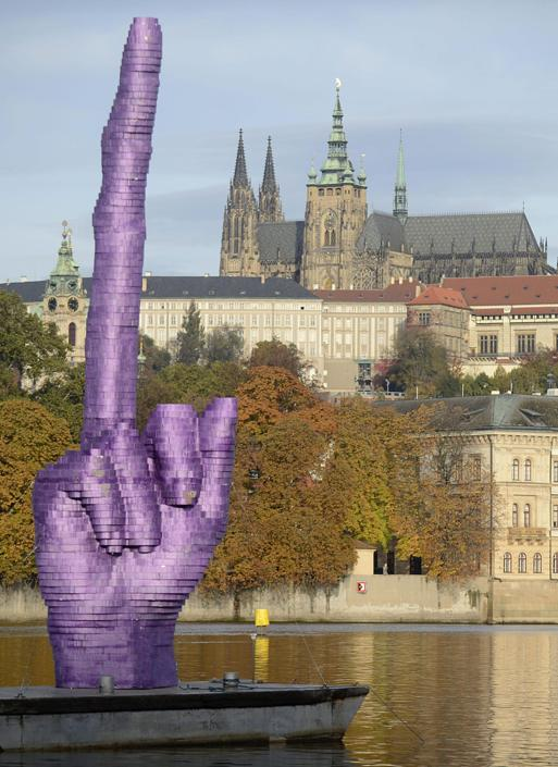 epa03917748 A view of a giant purple middle finger sculpture by Czech artist David Cerny on Vltava River in central Prague, Czech Republic, 21 October 2013. The artwork was installed 21 October morning, four days before the Czech early general election, on the Vltava River and is adressed to the Prague Castle (background), which is the seat of the Czech president. Controversial artist Cerny made several artworks commenting on the political situation in the country in the past years. EPA/FILIP SINGER